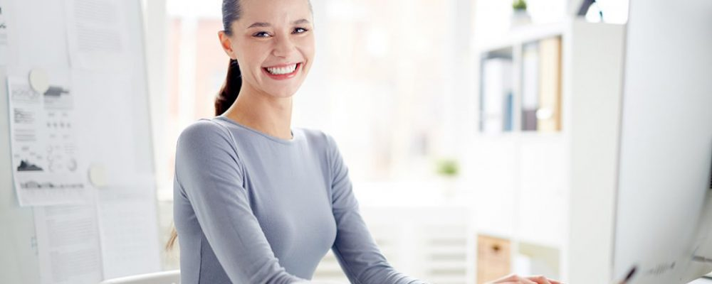 Young secretary looking at camera with toothy smile by her workplace while networking