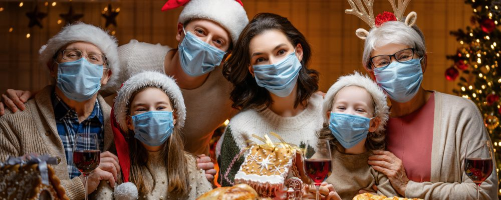 Merry Christmas! Happy family are having dinner at home. Celebration holiday and togetherness near tree. People are wearing facemasks.