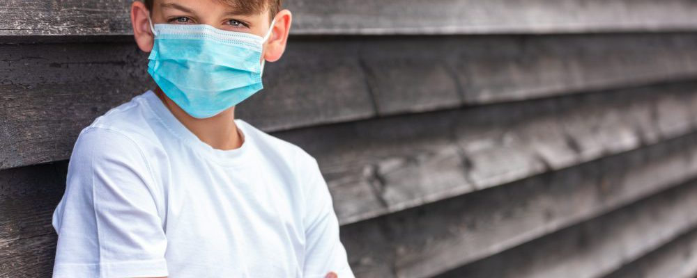 Boy teenager teen male child wearing a face mask outside during the Coronavirus COVID-19 virus  pandemic
