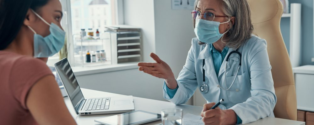 Mature female doctor in white lab coat making a prescription to young woman while sitting in her office